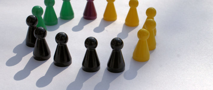 Coaching & Teamentwicklung. Eine Gruppe Spielfiguren, die im Kreis stehen.