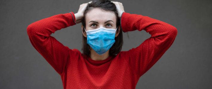 Frau im rotem Pulli mit Gesichtsmaske