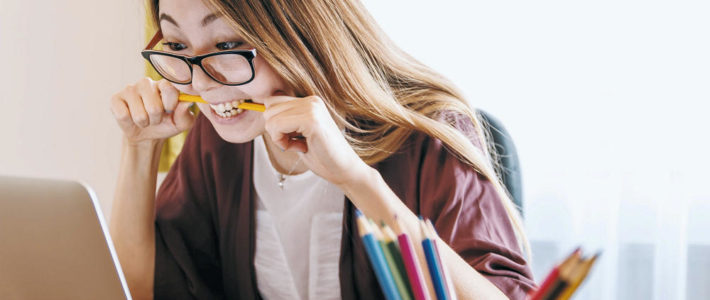 Junge Frau am Schreibtisch schaut auf ihren Laptop