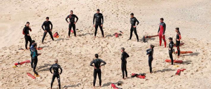 Gruppe von Menschen im Kreis am Strand